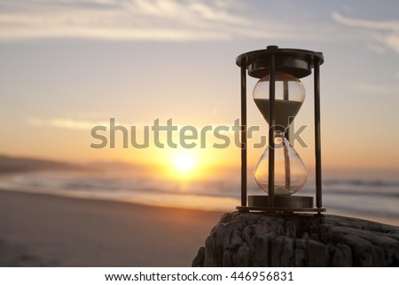 An hourglass on a beach in front of a beautiful sunrise, focus on hourglass.