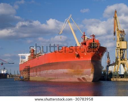 An huge ship during hull repair - stock photo