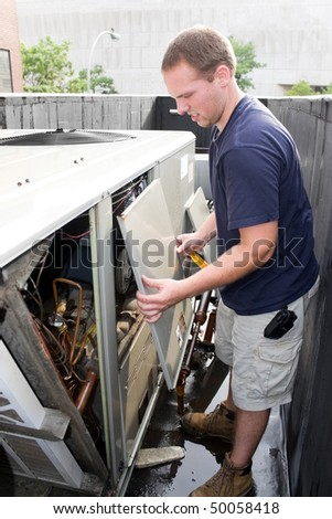 An HVAC heating ventilating air conditioning technician working on a large commercial unit. - stock photo