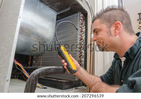 An Hvac technician searching for a refrigerant leak on an evaporator coil.  - stock photo