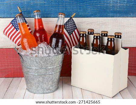 An ice bucket full of soda and a six pack of beer against a patriotic red, white and blue background. Perfect for Memorial Day and 4th of July themed projects. - stock photo