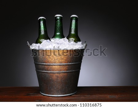 An ice bucket with three green beer bottles on a wet wood surface. Horizontal format with a light to dark gray background. - stock photo