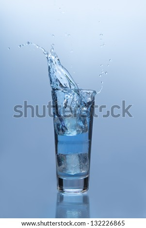 An ice cube falling into glass of water on blue background