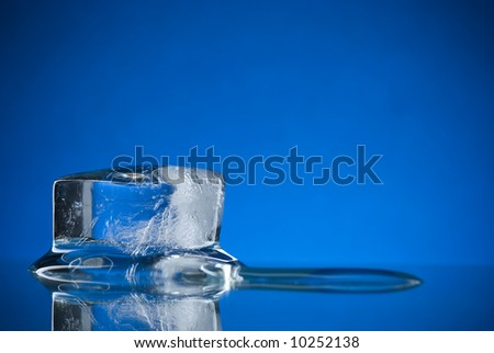 An ice cube on a reflective surface