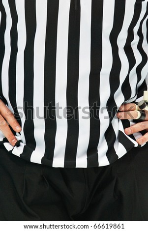 An Ice Hockey Referee is standing with his arms on his chest - stock photo