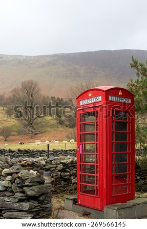 An iconic English telephone box in the Lake District National Park. The phone boxes were once important for communication but fell into disuse after mobile phones were invented. - stock photo
