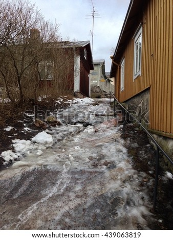 An icy path between old wooden buildings in Porvoo, Finland