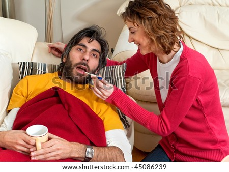 An ill husband is having his temperature checked by his wife. He's wrapped up on the couch and she's kneeling by his side. - stock photo