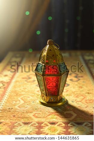 An illuminated arabic lamp on the carpet - stock photo