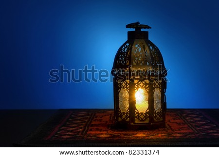An illuminated Arabic lantern on blue background - stock photo