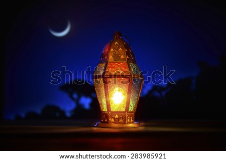 An illuminated colorful ramadan lantern against blue night sky with an crescent moon. - stock photo