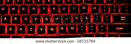 An illuminated keyboard glowing from multiple LEDs. - stock photo