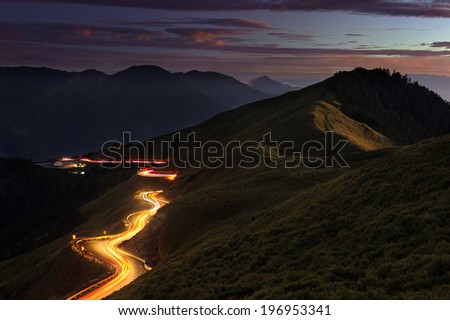 An illuminated road over the hills at night.