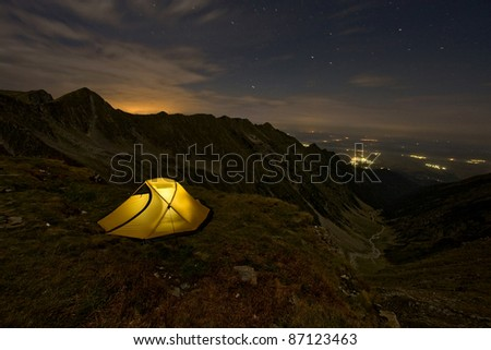 An illuminated tent in the night mounted above a valley in mountain and many villages lit - stock photo