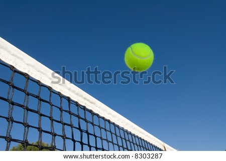 An image depicting the concept of tennis, including a ball gliding over the net in a blue outdoor setting - stock photo