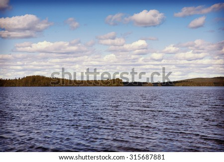 An image of a beautiful landscape from Finland. In this image a big lake is in front of the forest far away. Some clouds are in the sky. Image has a vintage effect applied.