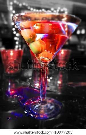 an image of a black white and color martini with olives