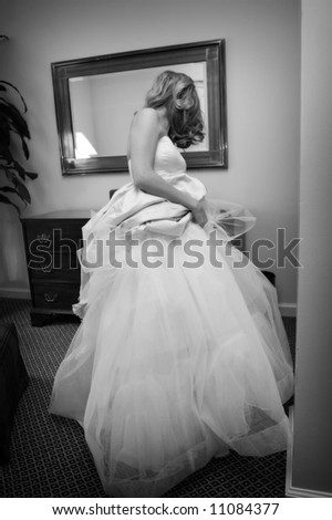 an image of a bride getting ready with her dress around her waist