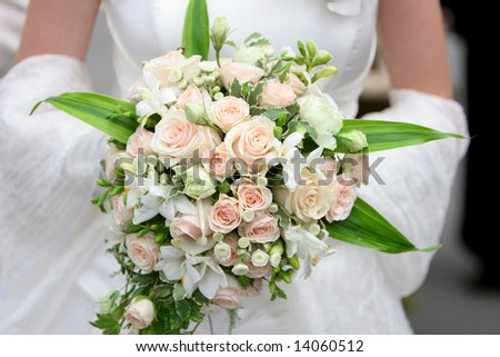 An image of a bride holding her bouquet of roses - stock photo