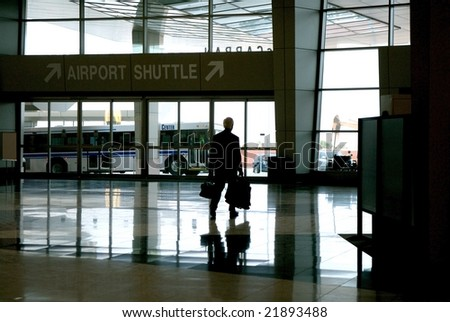 An image of a business man walking out of the airport - stock photo