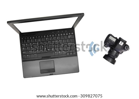 An image of a digital camera and laptop - stock photo