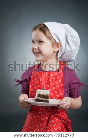 An image of a girl in a white hat with a cake on a plate - stock photo