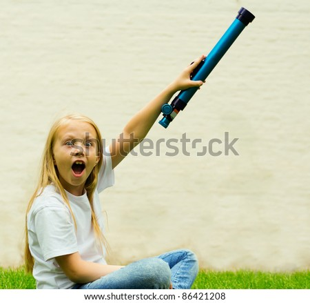 An image of a girl looking into a telescope - stock photo