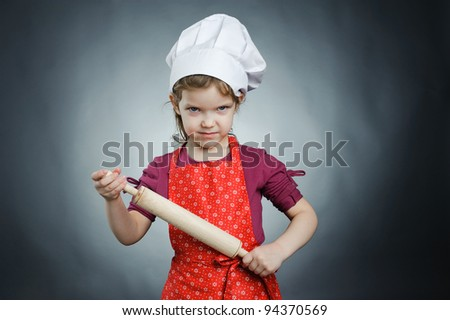An image of a girl with a rolling pin in her hands - stock photo