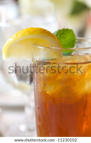 an image of a glass of ice tea on a sun drenched table - stock photo