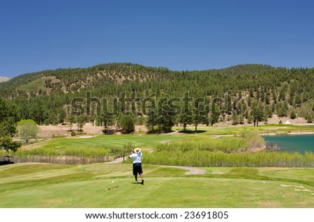 An image of a golfer following through on a swing - stock photo