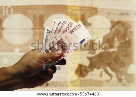 An image of a hand holding Euro currency with the continent of Europe as background. - stock photo