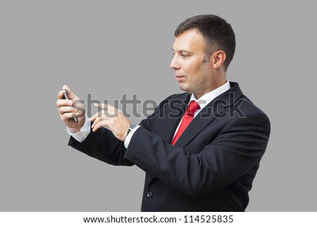 An image of a handsome business man and his mobile phone - stock photo