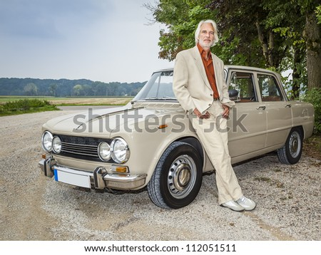 An image of a handsome man in front of his historic car