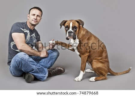 An image of a handsome muscle man with his dog - stock photo