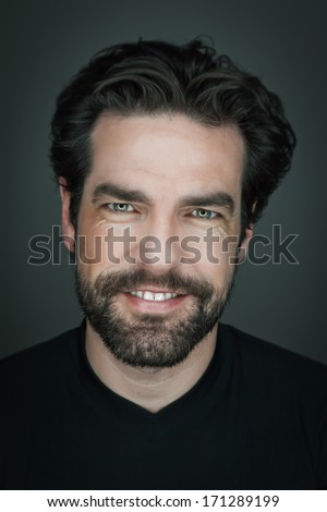 An image of a handsome smiling man with a beard - stock photo