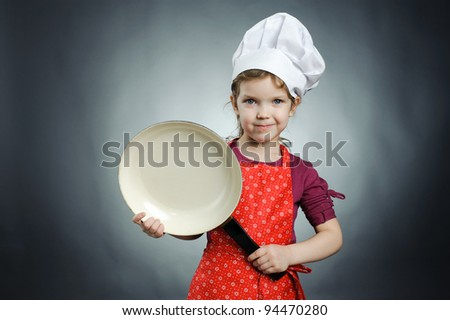 An image of a happy girl in white hat with frying pan - stock photo