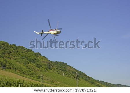 An image of a helicopter spraying crops on a difficult to access sloping hill in a valley - stock photo