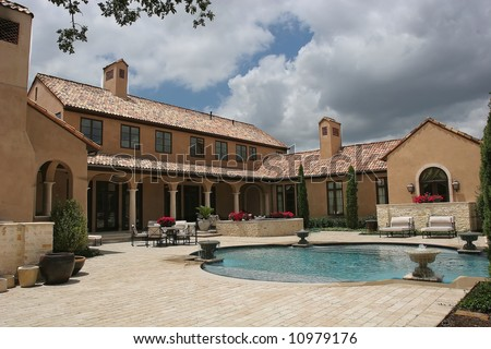 an image of a luxury home looking over the pool - stock photo