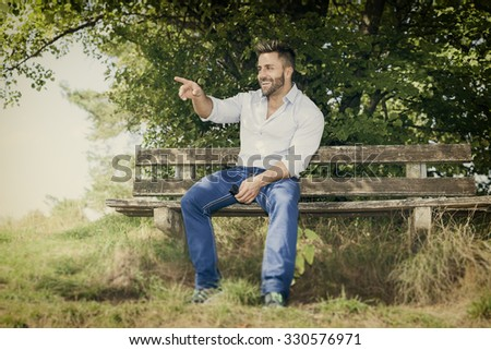 An image of a man outdoors pointing