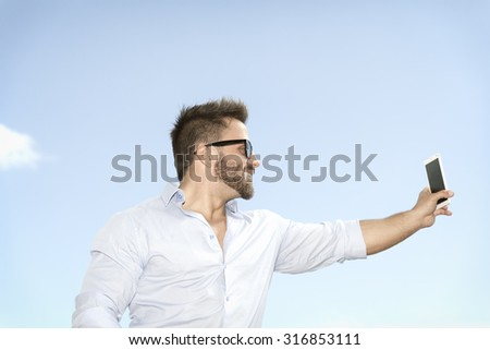 An image of a man taking a selfie with his smart phone