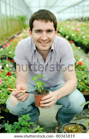 An image of a man with a plant in a pot