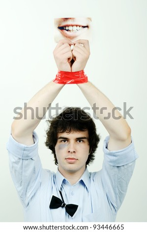 An image of a man with tape on his hands and a photo of a smile - stock photo