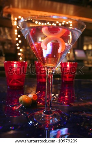 an image of a martini glass with a twist of lemon sitting on a wet bar - stock photo
