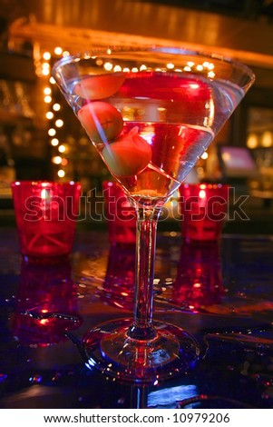an image of a martini with olives on a wet bar - stock photo