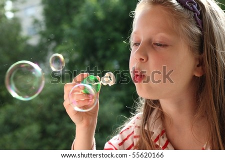 An image of a nice little girl making bubbles
