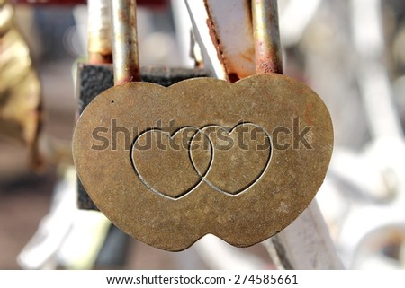 An image of a pad lock with two hearts engraved on it. It's considered in Russia if you lock it in some public place (e.g. on bridge etc.) on the wedding day it will bring you luck and happiness. - stock photo