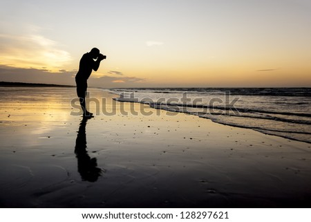 An image of a photographer at the sunset beach