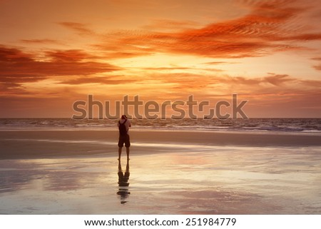 An image of a photographer at the sunset sea - stock photo
