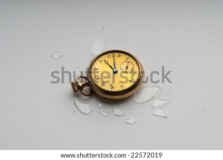 An image of a pocket watch broken on the ground - stock photo