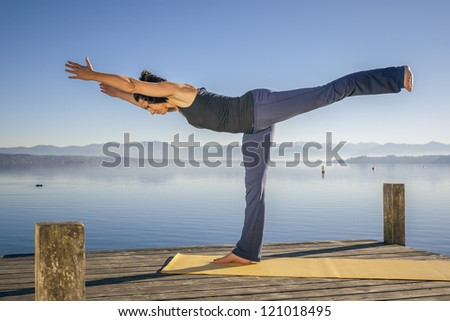 An image of a pretty woman doing yoga at the lake - stock photo